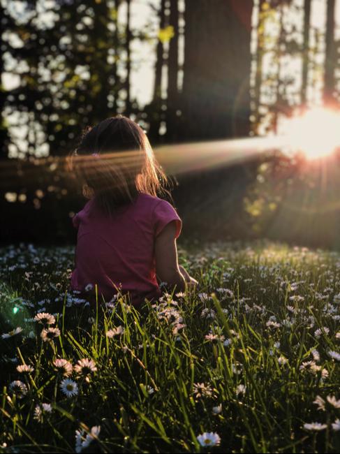little girl sitting outside in the sun